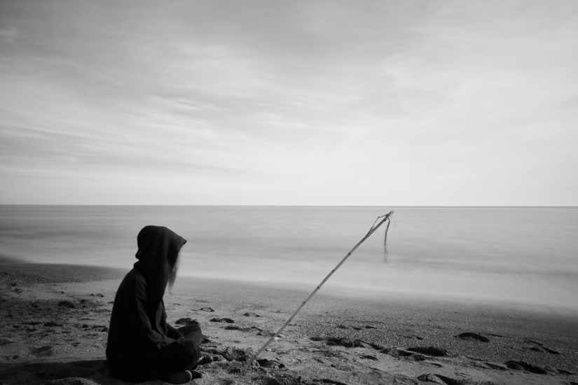 silhouette of woman with fishing pole sitting on bech